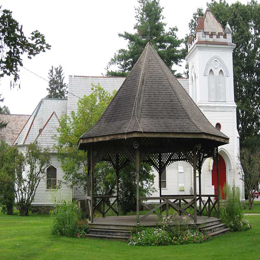 A Gazebo in front of a white church house in Greenwich, NY