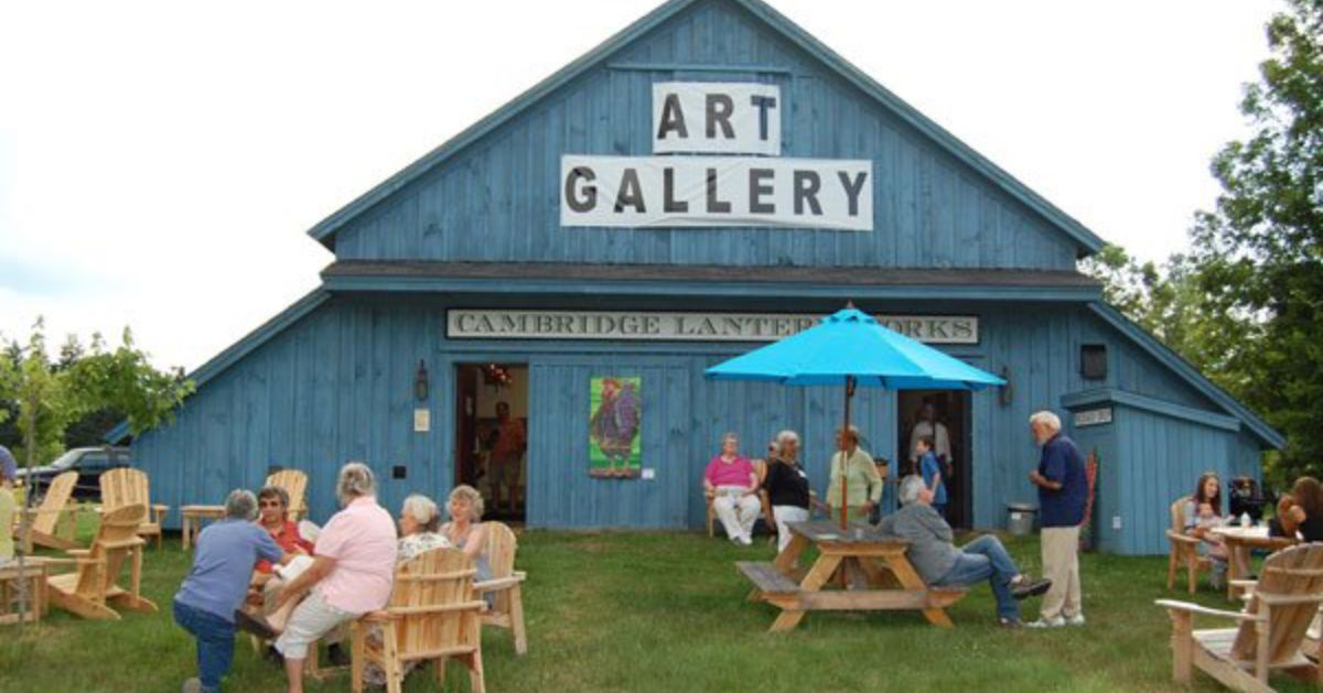 people outside a blue art gallery barn