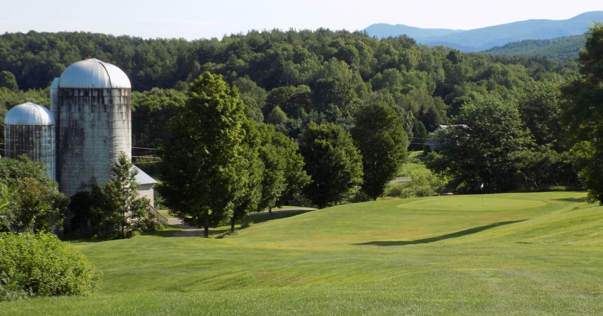 golf course with farm building nearby