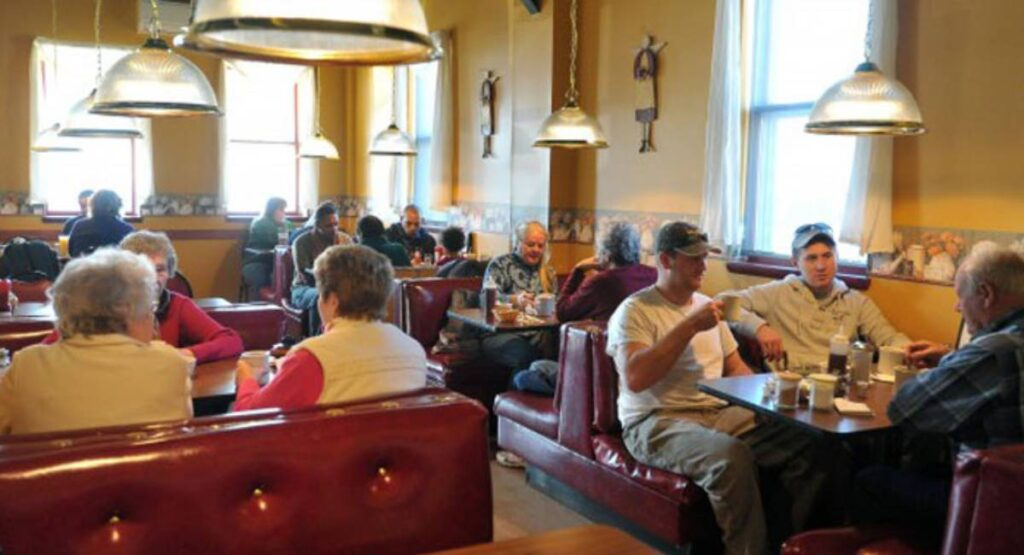 Several people sitting inside of Ginny Raes enjoying coffee and food.