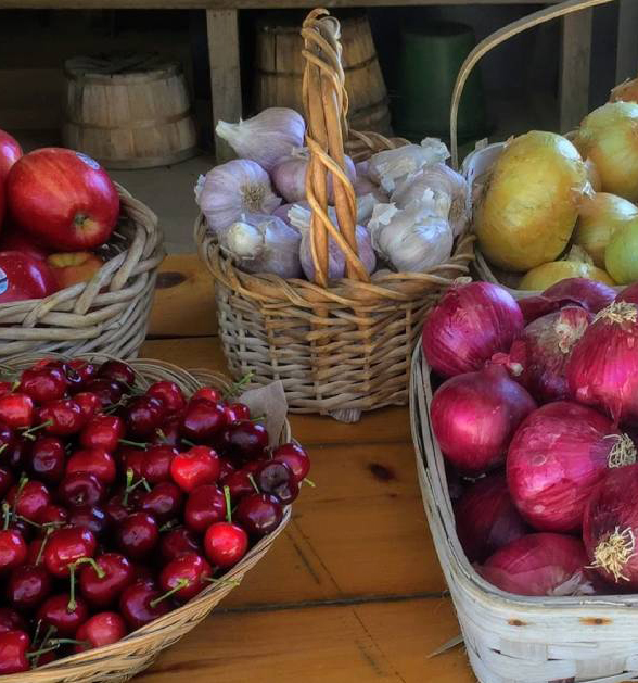 Close up of cherries, apples, red onions, white onions, and garlic in baskets.