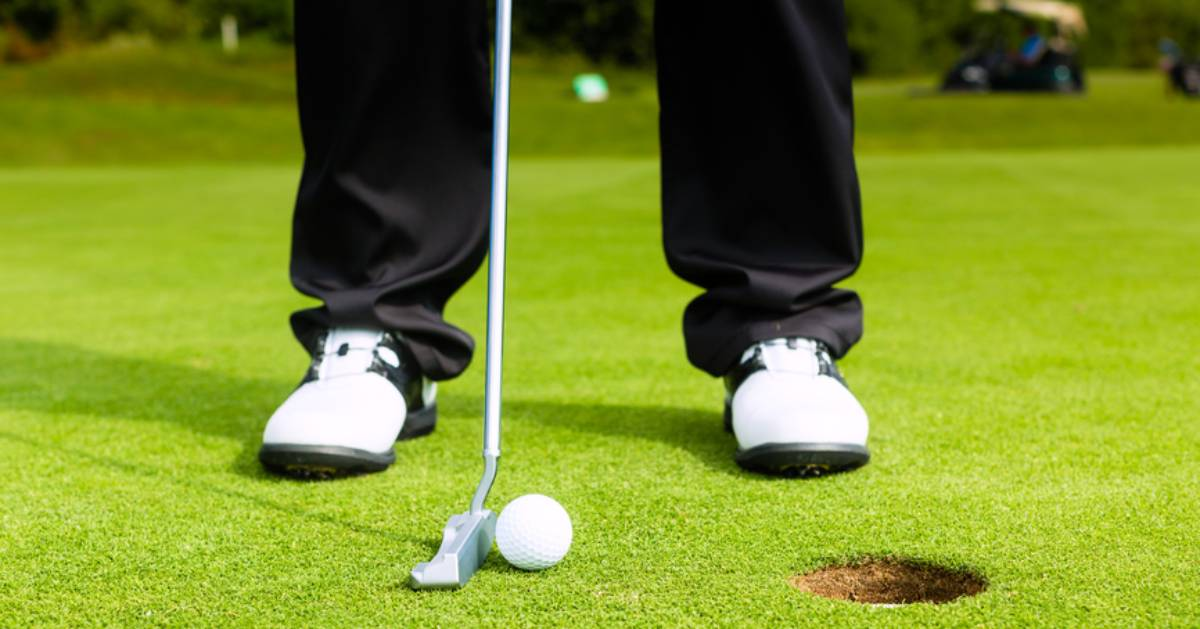 view of golfer preparing to putt the ball