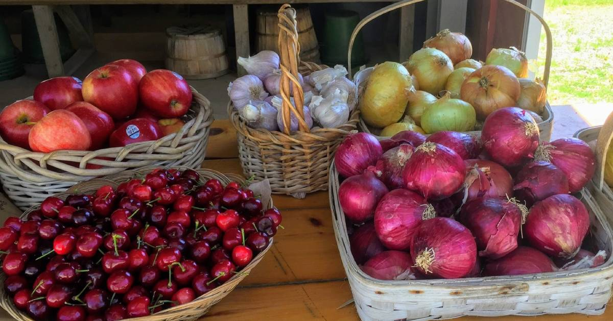 cherries, apples, garlic, and onions on a table