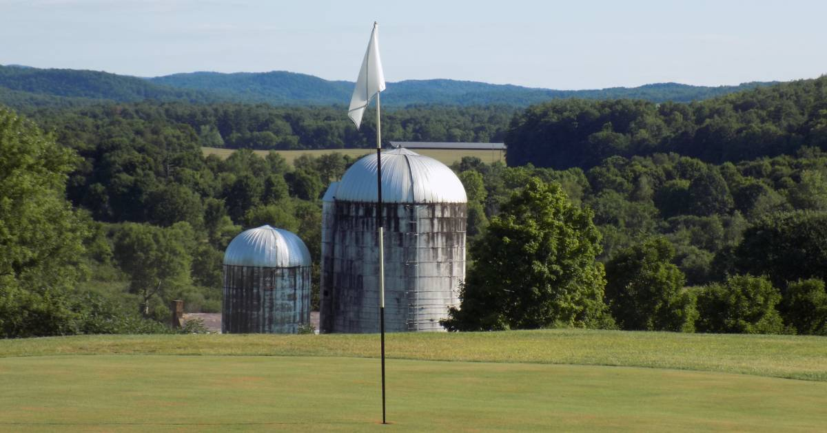 golf hole on course with farm building in the background view
