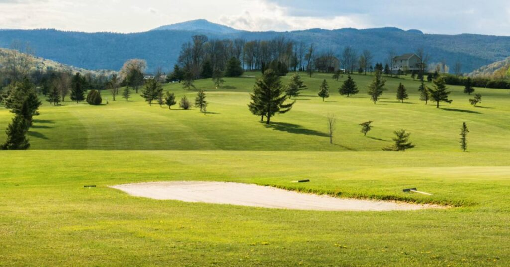 Another golf course view with beautiful green grass and mountains in the background.