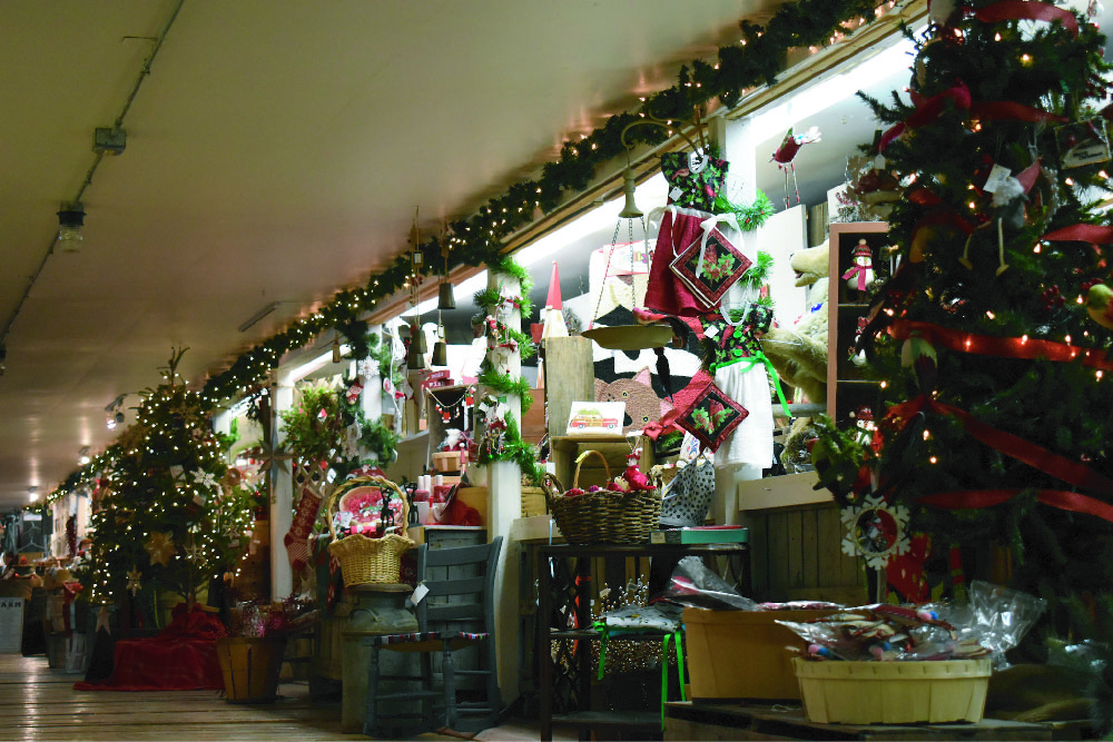 Interior of a store wall decorated with Christmas ornaments and several Christmas items that can be purchased.