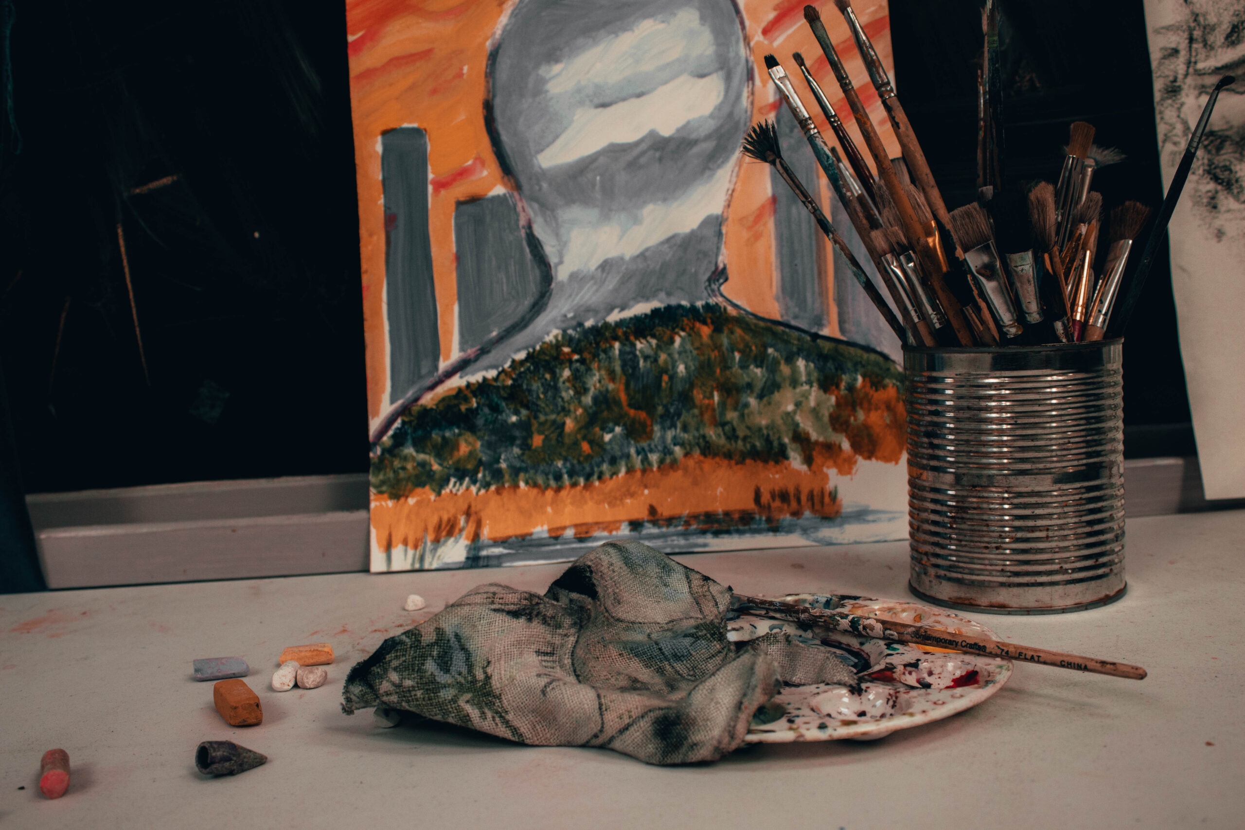 A metal can holding brushes and a painting is seen behind it