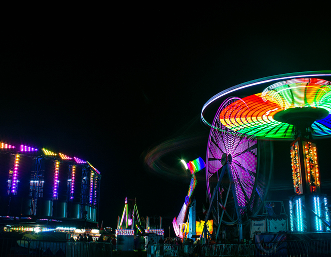 Carnival rides with bright lights against a night clear sky