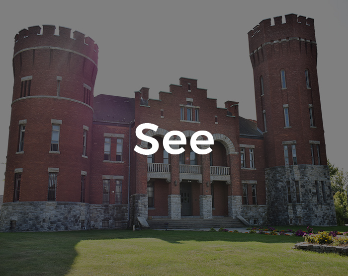 A castle-like building with red bricks and the word See overlaid on it.