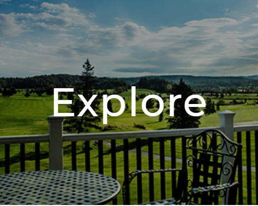 A table on a balcony overlooking a beautiful green field with a blue sky. The word Explorer is overlaid on it.