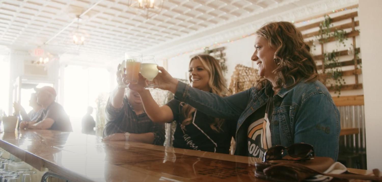 Women at bar raising beer glasses at craft brewery near Lake George