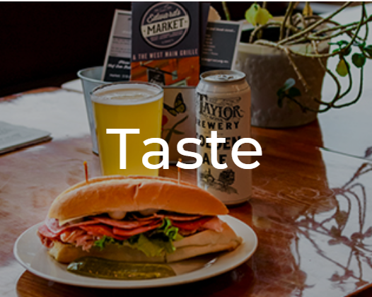 A table with a sandwich and beer on it. It is decorated with the restaunrant menu and a small plant. The word Taste is overlaid on it.